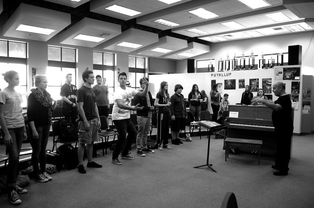 Choir Director George Guenther warms up some of the cast of