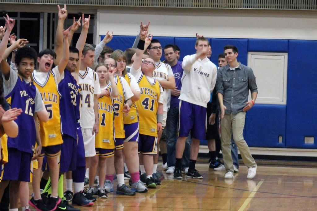 Puyallups Special Olympics basketball team lines up on the side of the court before their game Jan. 27 and puts viks up.