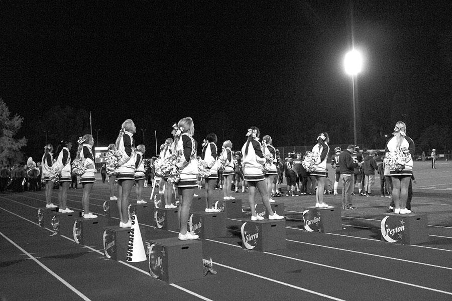 The cheer team takes a break from cheering during a home football game earlier this fall. Stunts performed at both practices and games like these are what prepared the girls for their competition this winter.