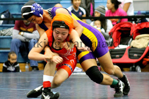Sophomore Justine Tulaepa goes for a take down against her opponent from Lakes High School.