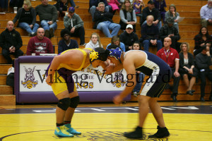 Junior Ryan Tyler Espinoza ties up with his opponent at the beginning of his match.