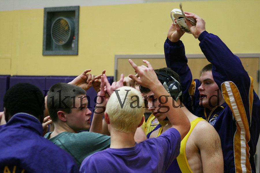 """The Puyallup wrestling team huddles and puts """"viks"""" up before the tournament starts."""