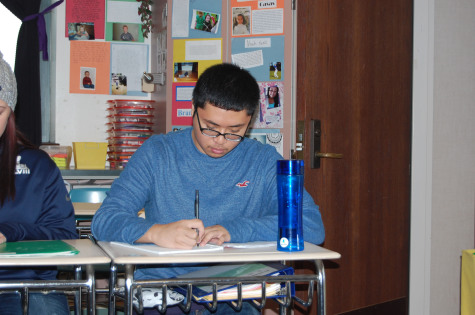 Senior Christian Buensuceso takes notes in his AP Literature class.