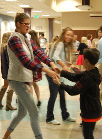 Senior Addie Picha dances with a little boy.