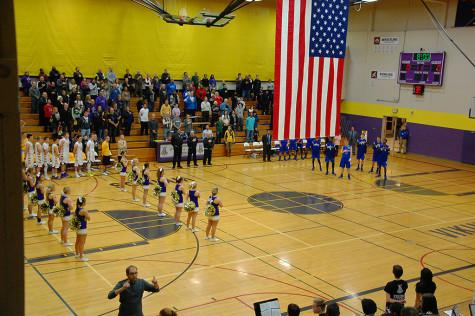 """Spectators stand during the """"Pledge of Allegiance."""" The boys basketball team lost to Curtis High School Jan. 20 with a score of 68-75 after going into overtime."""