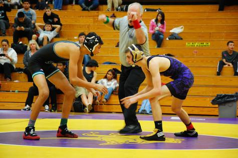 Senior Tyler Grajek stares down his opponent as the referee blows the whistle for the match to begin. The wrestling team won 49-18 against Spanaway Lake High School Jan. 21.