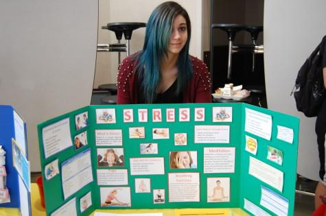 Senior and HOSA member Dalal Alghanmi poses behind her display featuring the affects of stress.
