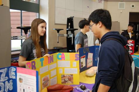 Sophomore and HOSA member Hannah Custer explains the difference between fats, carbohydrates and proteins to junior Tae Kim. The Health Occupation Students of America club held their annual spring health fair March 26.