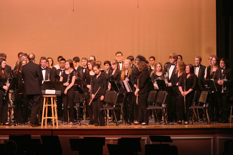 The Wind Ensemble stands up to be recognized after their performance. The Percussion and Wind Ensemble along with the Jazz, Concert and Symphonic Bands performed March 23 at the band concert held in the auditorium.
