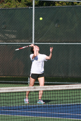 Junior Kaylee Oliva tosses the ball in the air in preparation to serve to her opponent. The girls tennis team faced Graham-Kapowsin High School March 26 and lost with a score of 1-4.