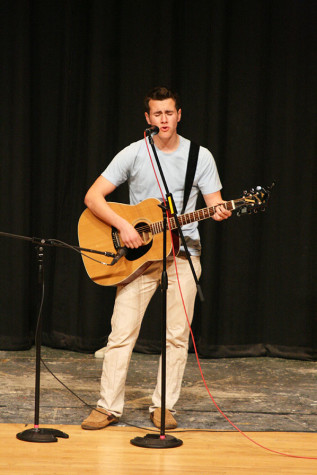 "Senior William Ruchti performs his version of Jason Aldean's ""Trying to Love Me,"" while playing the guitar. The Viking Varieties talent show was held April 9 in the auditorium."