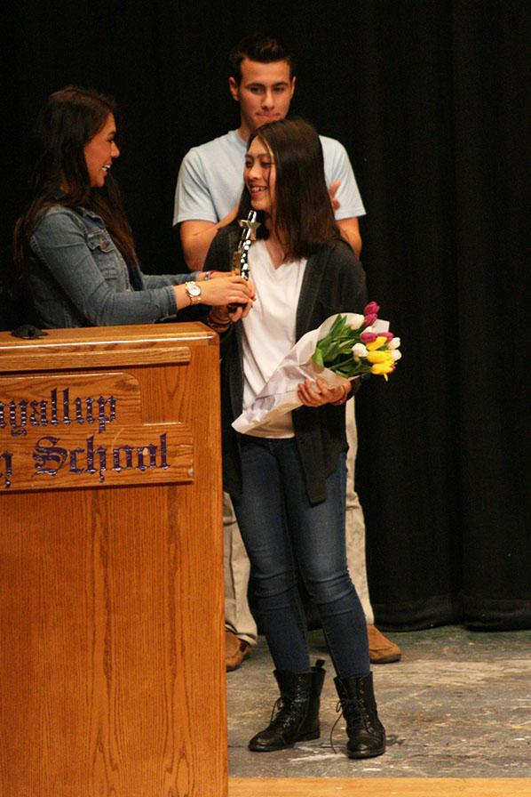 Emcee senior Celeste Grinnell awards her sister, junior Olivia Grinnell with the first place trophy. The Viking Varieties talent show was held April 9 in the auditorium.