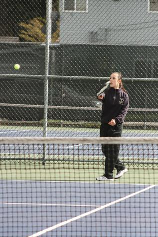Sophomore Jessi Oyama warms up before her doubles match begins with sophomore Scotney Carlson as her partner. The girls tennis team played against Spanaway Lake High School April 14 and won with a score of 4-1.