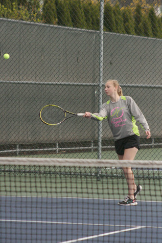 Sophomore Scotney Carlson warms up before her doubles match begins with sophomore Jessi Oyama as her partner. The girls tennis team played against Spanaway Lake High School April 14 and won with a score of 4-1.