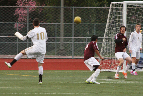 Junior Trevor Lee kicks the ball towards the goal, hoping to score. The boys soccer team won against Bethel High School with a score of 7-0 April 21.