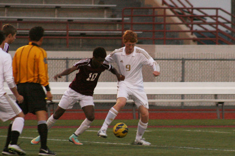 Junior Levi Woolley attempts to fight off a defender. The boys soccer team won against Bethel High School with a score of 7-0 April 21.