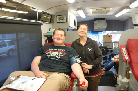 Sophomore Dawson Thompson smiles as he gives blood in the bus. HOSA held their last blood drive of the 2015 school year on June 1.