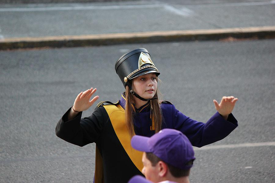 Senior Amy Kranz directs the Puyallup High School band in preparation for the march to the match on 9/18/15.