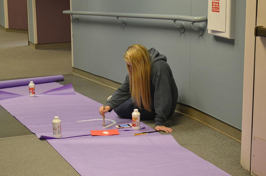Sophomore Gabby Horton paints a poster in the hallway advertising the homecoming theme Greek week