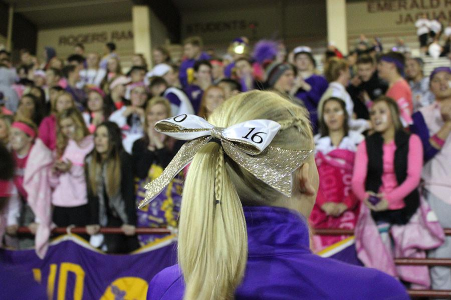 A cheerleader gets ready to cheer with the student section at the football game on 10/23/15.