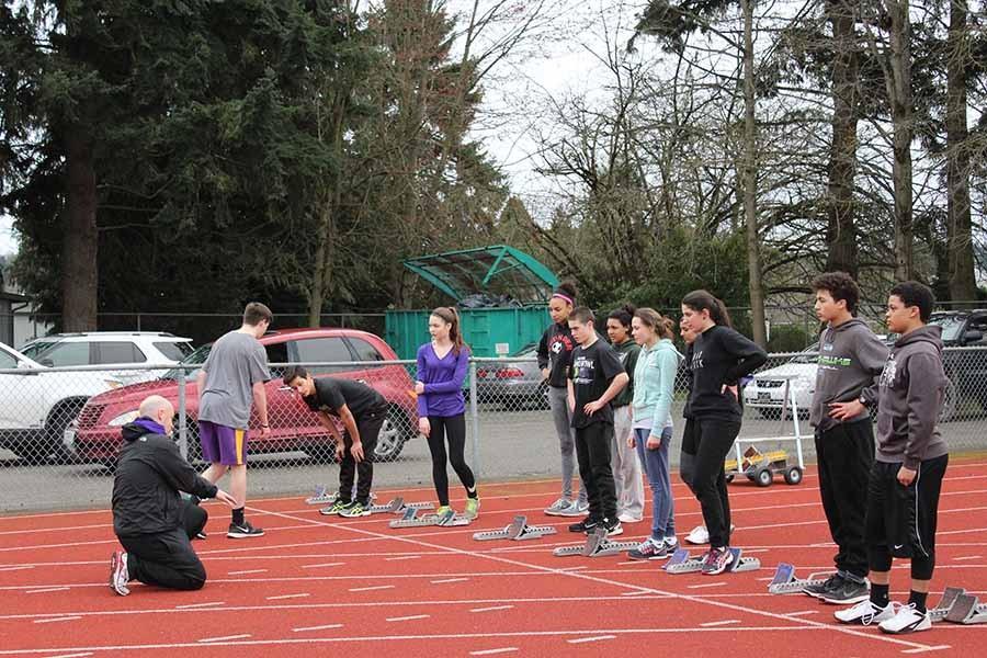 Coach Fleisch helps runners with the blocks. Sparks stadium track practice.