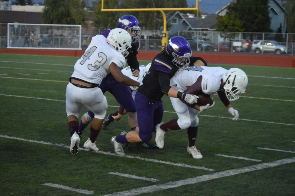Puyallup High School Vikings football team playing against the South Kitsap Wolves. Number 42, Kyler Johnson, tackling a player from the opposing team.