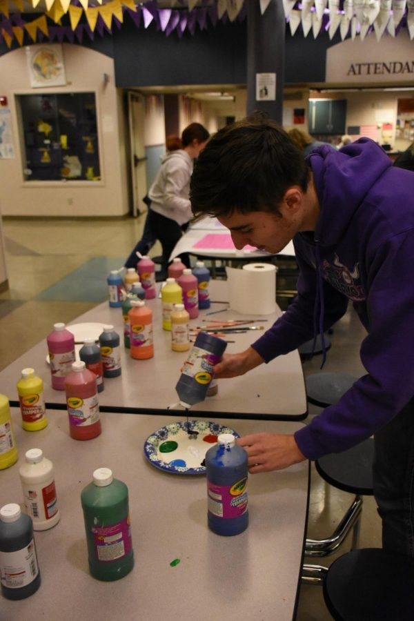 "Senior Winter Roberts gets paint to decorate his tile with. ""I went in with no idea what I was going to paint. There's a lot of pressure to... leave something worthwhile behind"" Roberts said. Students painted tiles in the commons while listening to classical music."
